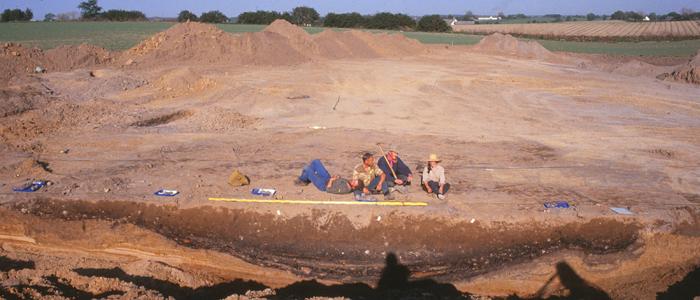 Fra udgravningen ved Persano 1994. En af de usædvanligt store lertagningsgruber er gennemgravet med maskine. Størrelsen antydes af personerne på billedet!