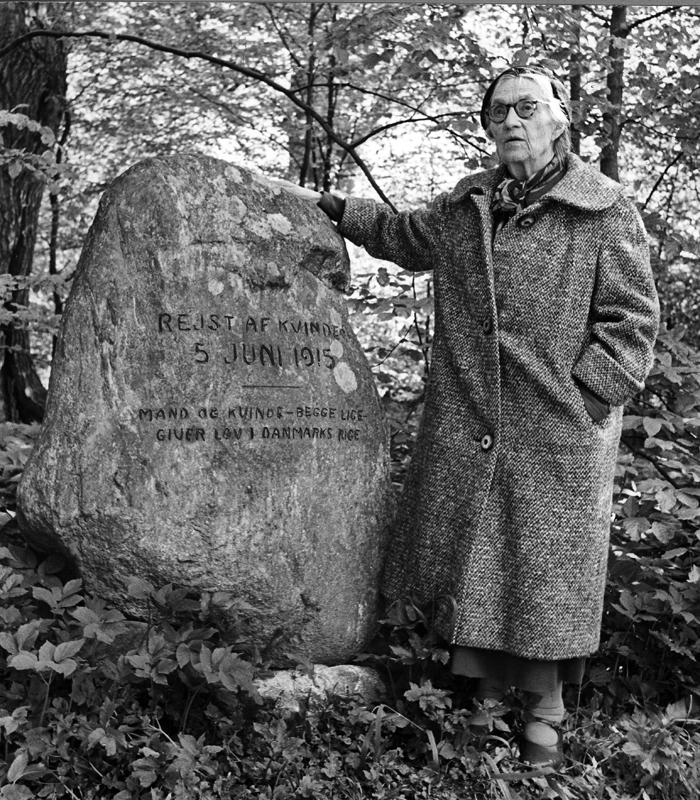 Rigmor Hansen (1880 - 1969) var gift med Laurids Hansen (1876 - 1954), der var redaktør på Frederiksborg Amts Avis fra 1901 til 1954. Han havde skrevet en prolog, som Rigmor læste op ved indvielsen af mindestenen på Fredspladsen i Lille Dyrehave den 15. juni 1915.      Ved et velbesøgt 50 års jubilæumsarrangement i 1965, holdt på Luthersk Missions Højskole tæt ved Fredspladsen, fremsagde hun de samme vers. På billedet besøger hun stenen samme dag. Bemærk, at stenen den gang stod på en cementsokkel.